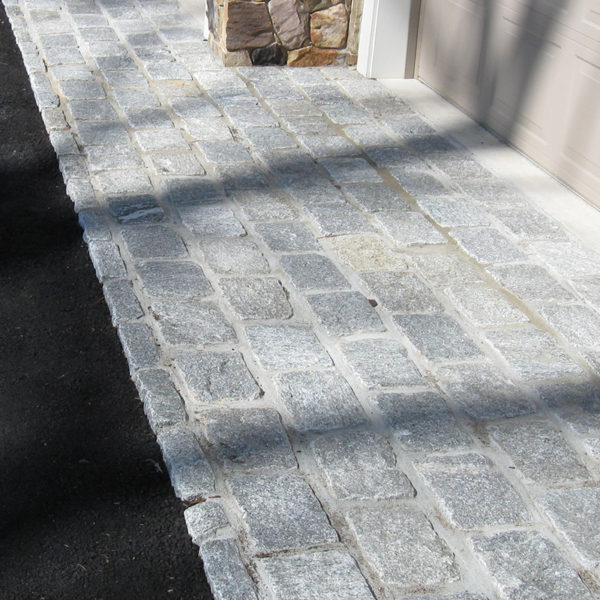close up of cobblestone installed in front of a garage, in a driveway