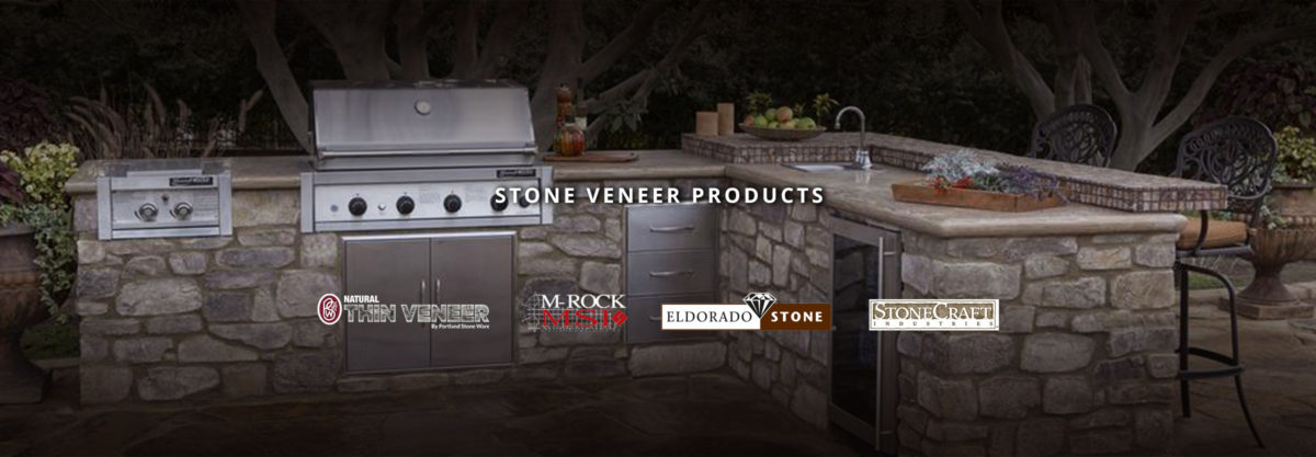 an outdoor stone kitchen with a grill, sink, fridge, and cabinets