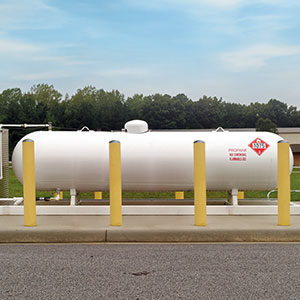 white oil tank with yellow bollards surrounding it