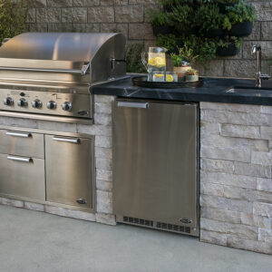Outdoor kitchen with a grill, fridge, water pitcher and cabinets built with stone
